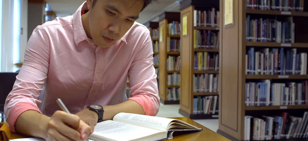Young man at Asia campus studies in library.