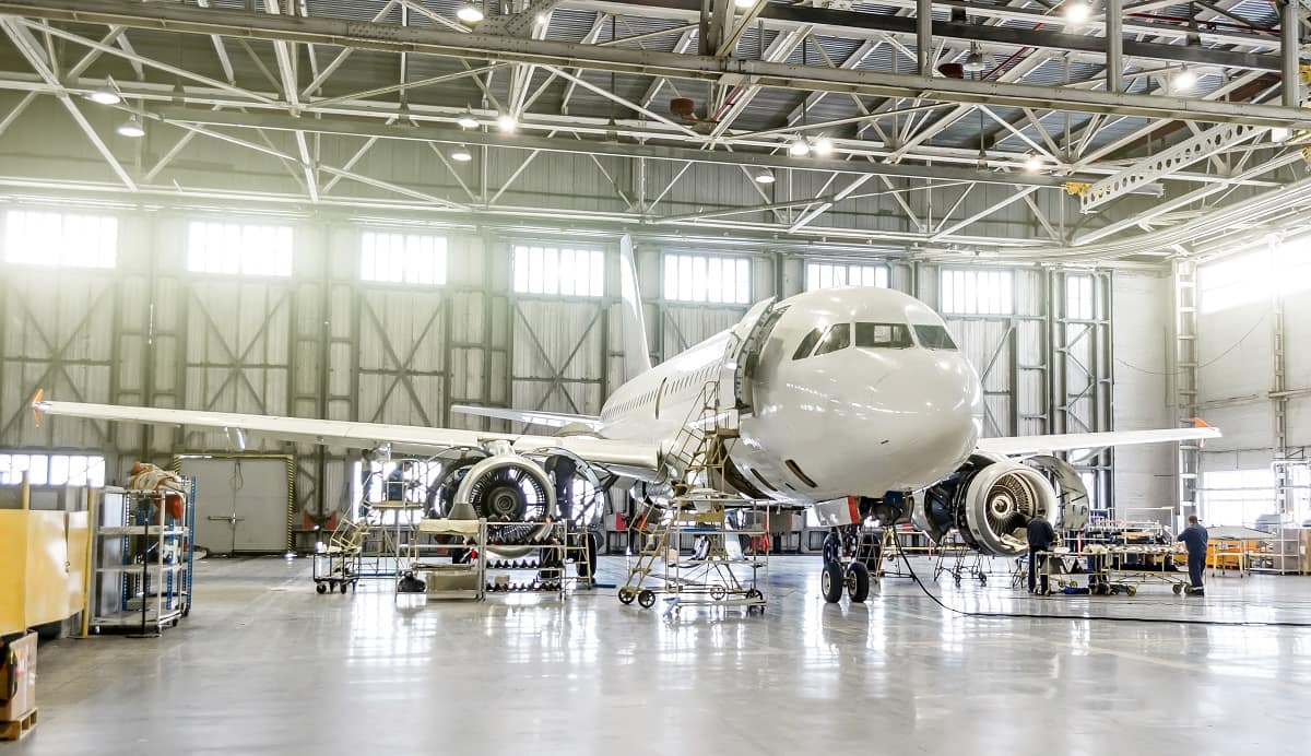 Commercial airliner is worked on in a hangar by aviation maintenance technicians.