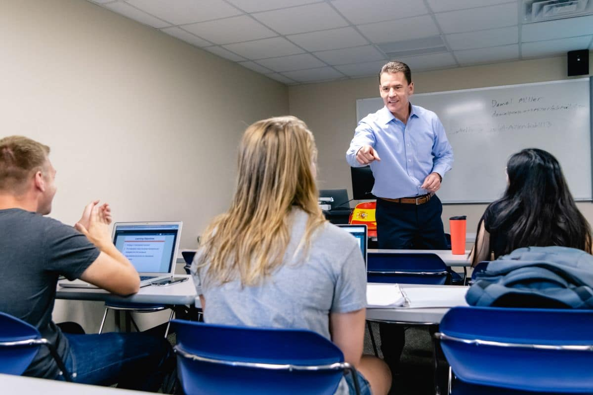 Dr. Thomas Drape, Director of Prescott's School of Business, engages students in a classroom discussion about business