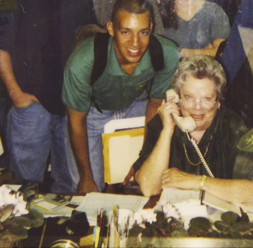 Old photo of Dottie Crawford on the phone with students in the background