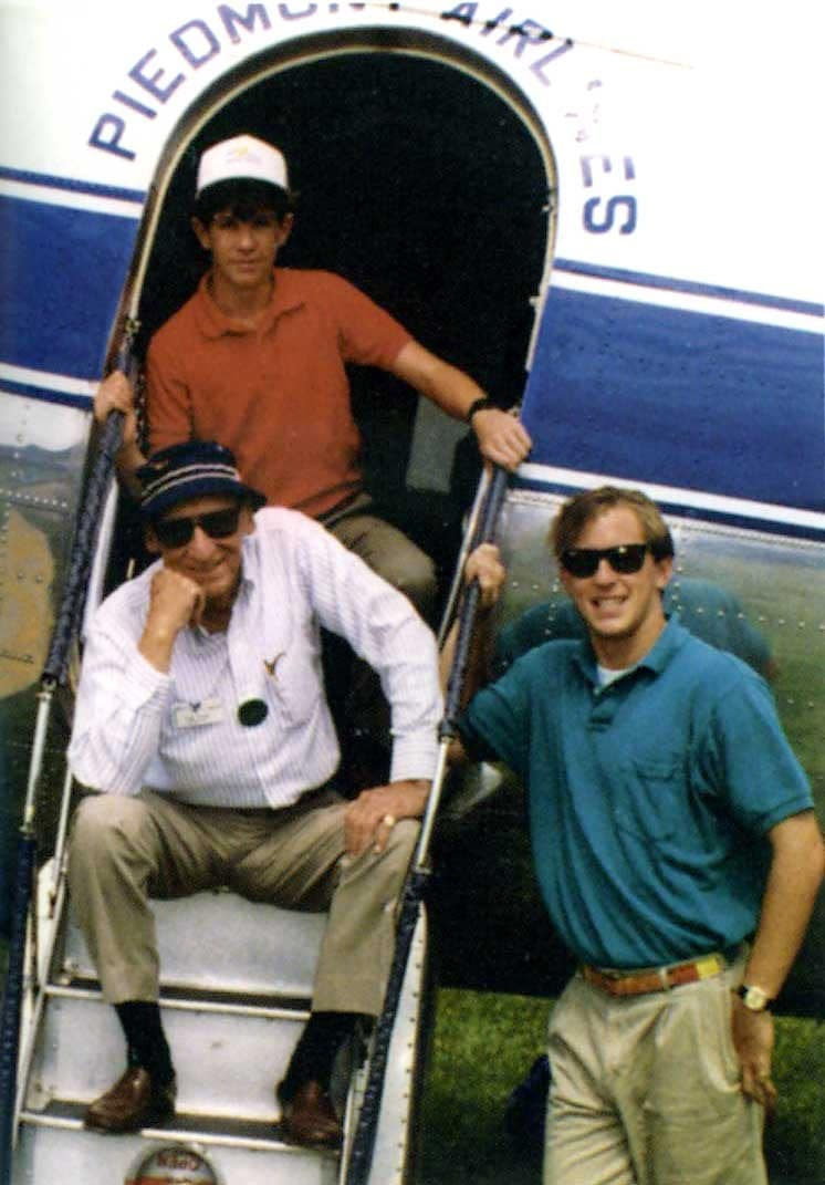 Tom Davis with grandsons, seated in on a Piedmond Airlines airplane exit staircase