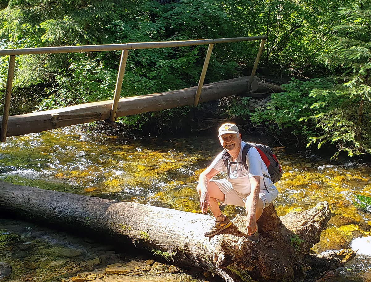 Warren Childers sitting on a log by a stream