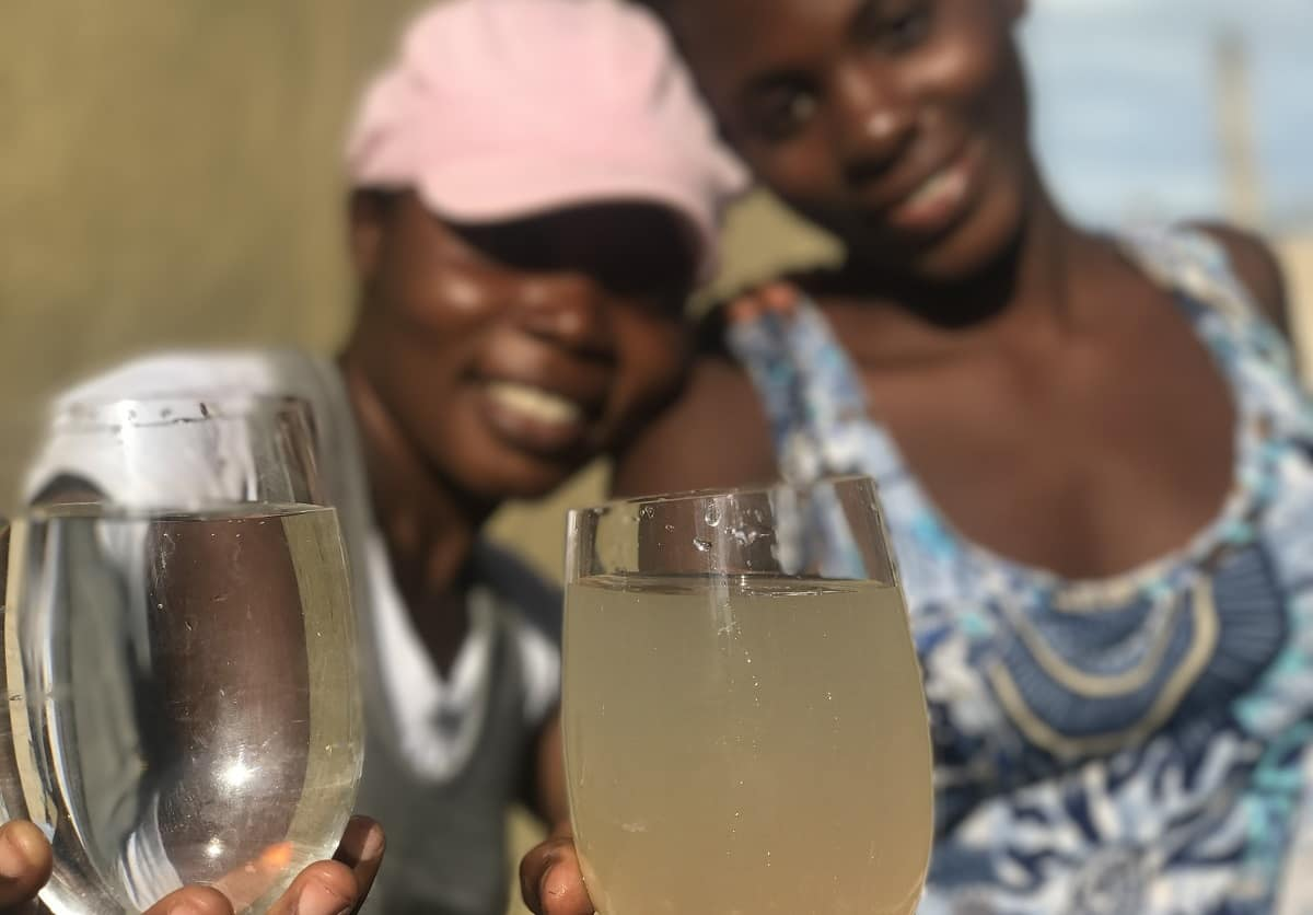 Haitian women hold glasses of purified and unpurified water