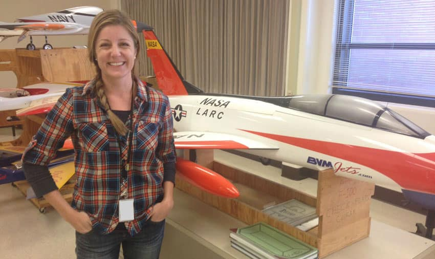 Jill Brown, NASA engineer and Worldwide student, stands in front of a model jet
