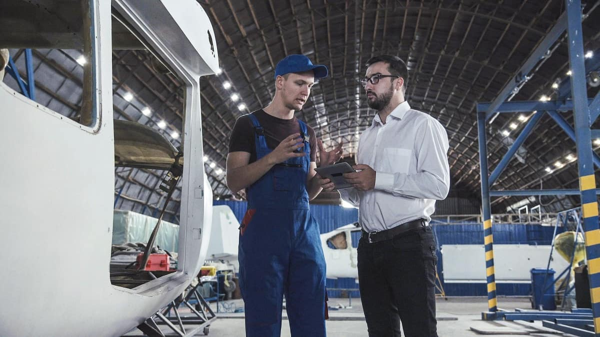 Mechanic and Engineer talk in a hangar near airplanes.