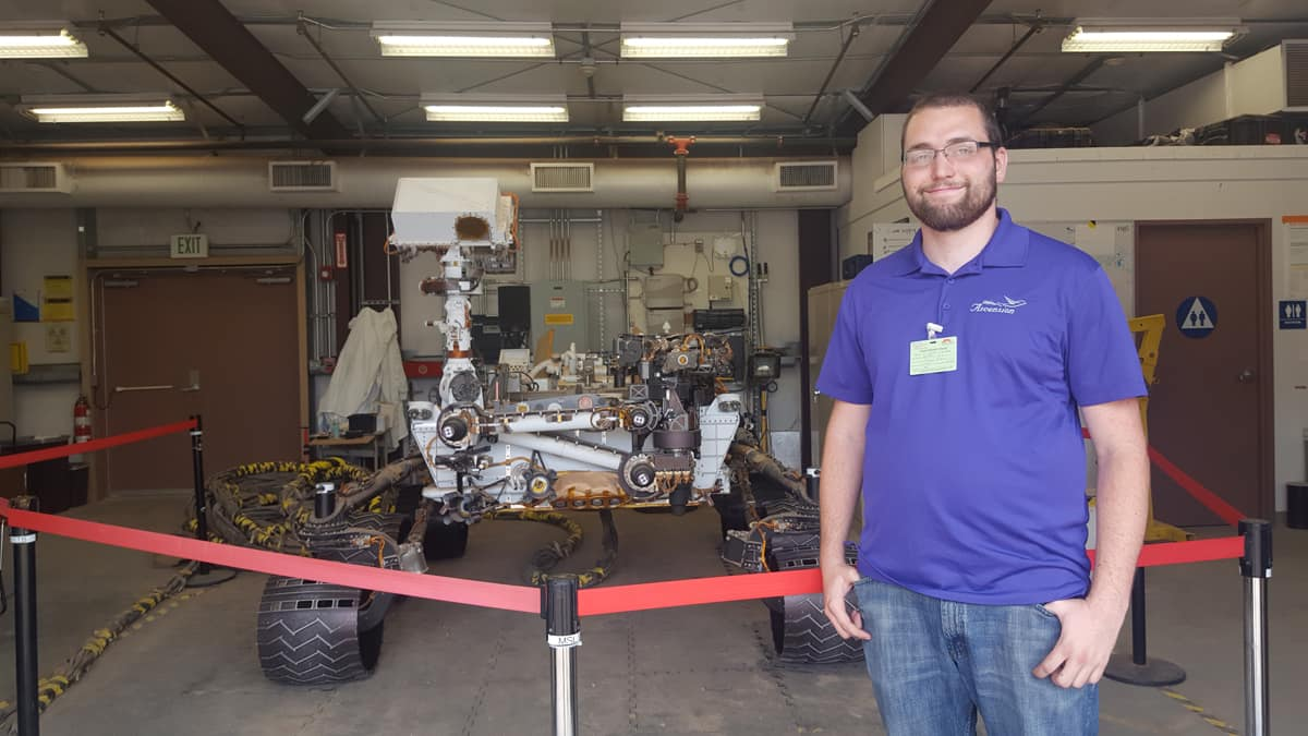 Embry-Riddle Eagle Matthew Demi Vis, now an avionics engineer at the Jet Propulsion Laboratory, at work with a copy of the Mars Curiosity Rover.