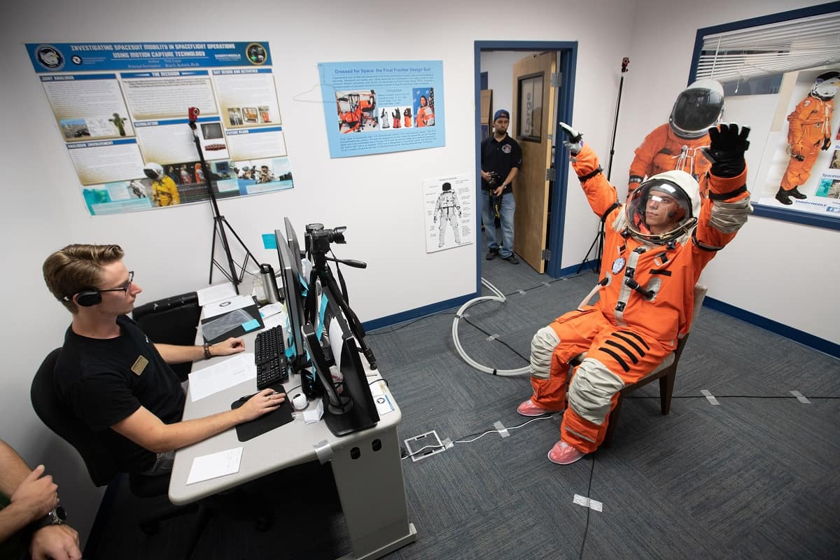 A student wearing an orange space suit with raised arms in front of a student sitting at a computer.