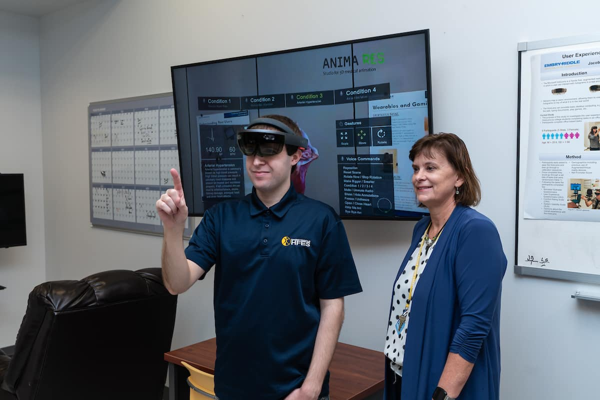 Dr. Barbara Chaparro, professor of Human Factors and Behavioral Neurobiology, coaches Ph.D. student William Shelstadt as he demonstrates a Microsoft HoloLens augmented reality headset connected to a medical training application in the RUX (Research in User eXperience) Lab.