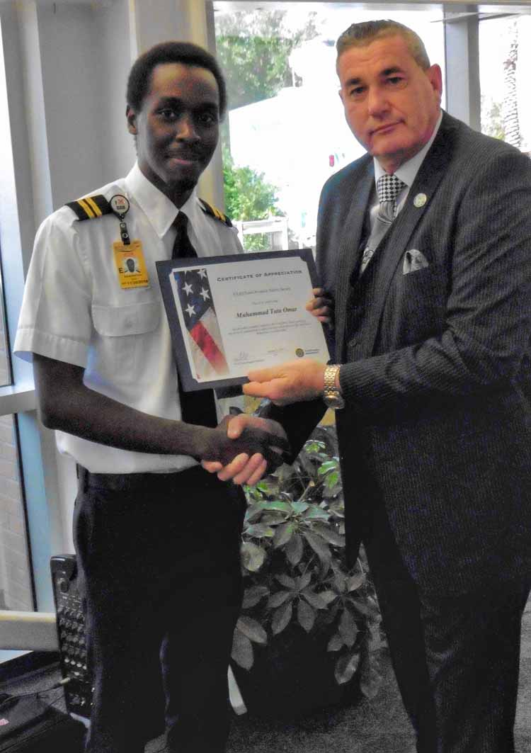 Flight Instructor Muhammad Omar receives an FAA Safety Award from FAA Orlando Flight Standards District Office Manager Max McConnell.