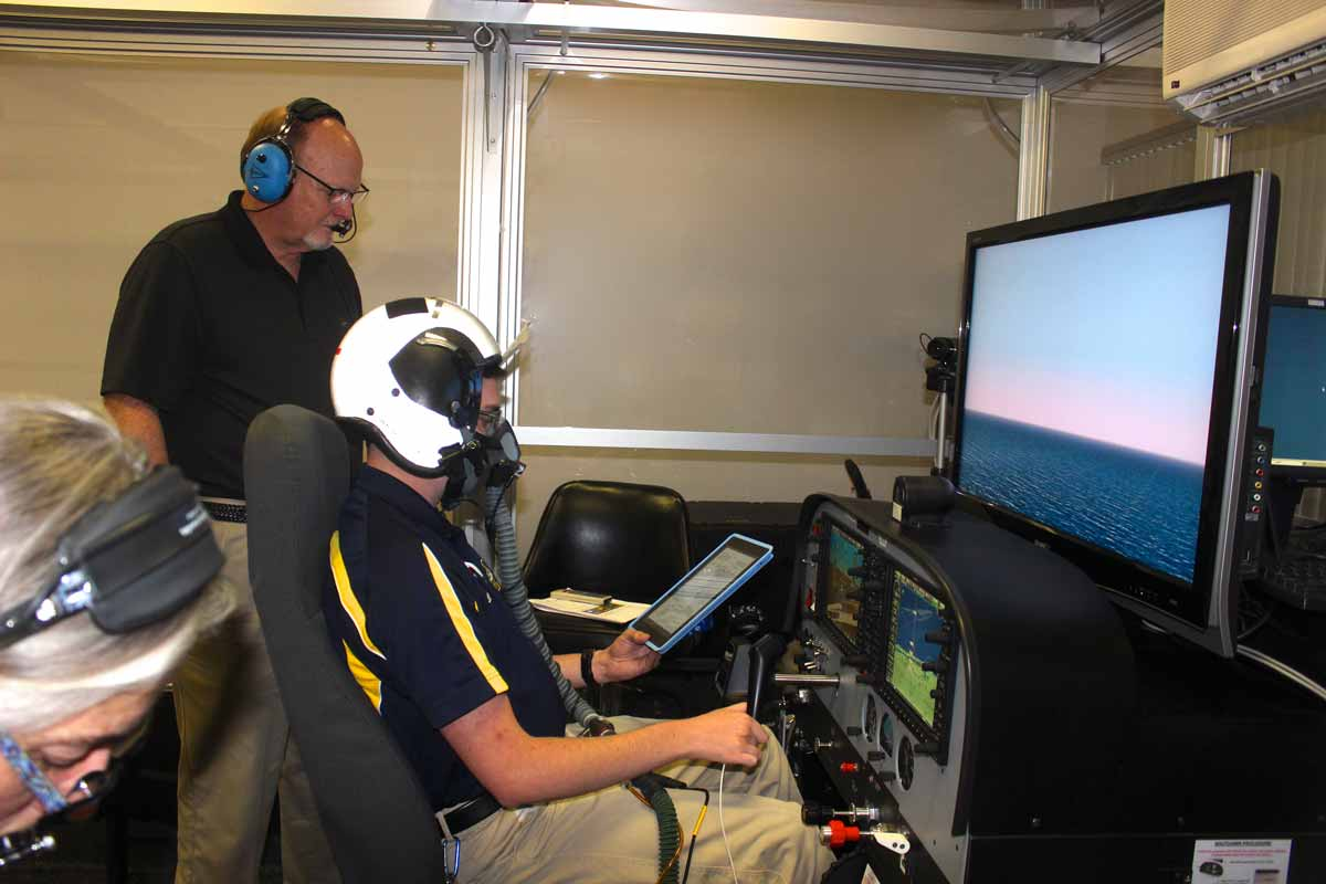 Inside Embry-Riddle's High-Altitude Laboratory, Joshua Swain took part in pilot hypoxia training, answering questions about his symptoms as he flew a simulated instrument approach, monitored by faculty member Michael Coman. Swain graduated in 2017 and now works as a Geospatial Analyst, specializing in Aeronautical Safety of Navigation for the U.S. Department of Defense.