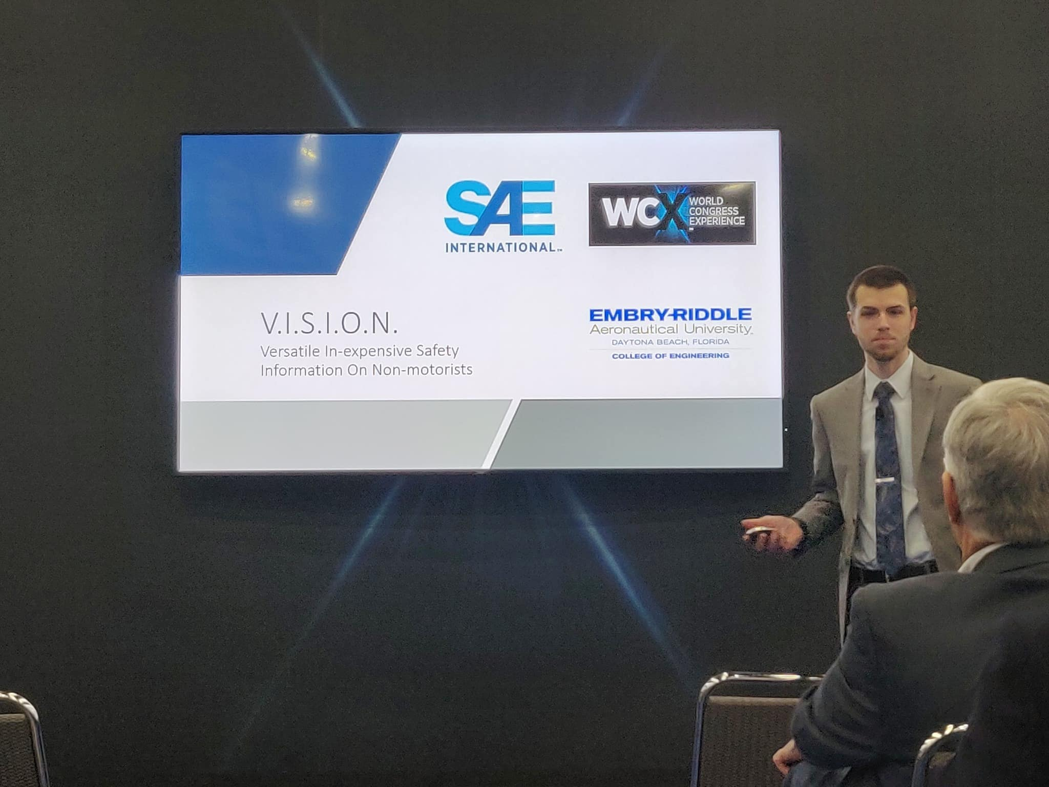 Andrew Ferree presents his and Zack Siadman's idea for a vehicle-to-bicycle communication device to executives at the SAE International's Connected Vehicle Challenge 2019, where the duo won 2nd place overall. (Photo: Zack Saidman)