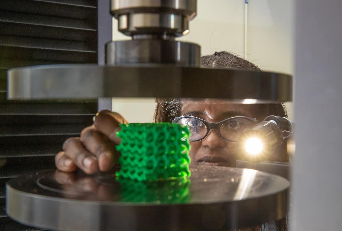 One of Dr. Ali Tamijani's students, Rossana Fernandes, positions a honeycomb sample object to test the performance of optimized cellular structures in the Structures Lab at Embry-Riddle's MicaPlex facility. (Photo: Embry-Riddle/David Massey)