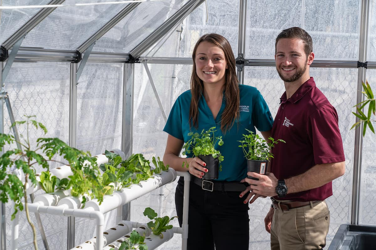 "Recent graduate Deanna DeMattio, a flight instructor, and current student Nicholas McGuire use a greenhouse and hydroponics to grow ""superfoods"" that could be used to feed astronauts on Mars."