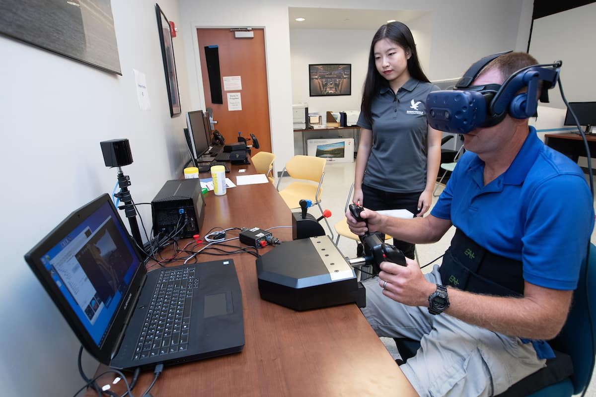 "Graduate students Qianhong ""Echo"" Liu and Tyson Richards work on a virtual reality Spatial Disorientation Simulator."