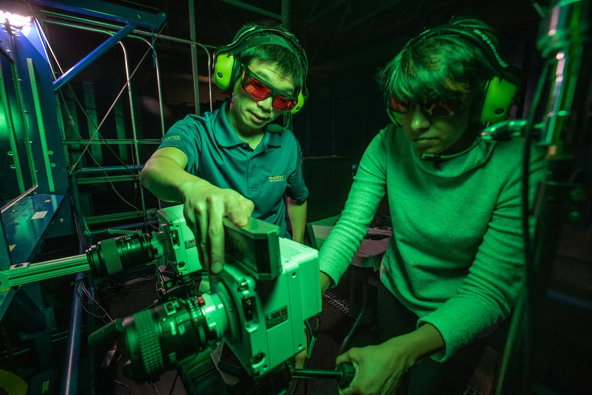Dr. Zheng Zhang (left) works with Ph.D. candidate Dhuree Seth to prepare high-speed cameras inside Embry-Riddle's wind tunnel, as part of an effort to study the airwake of a model U.S. Navy frigate.