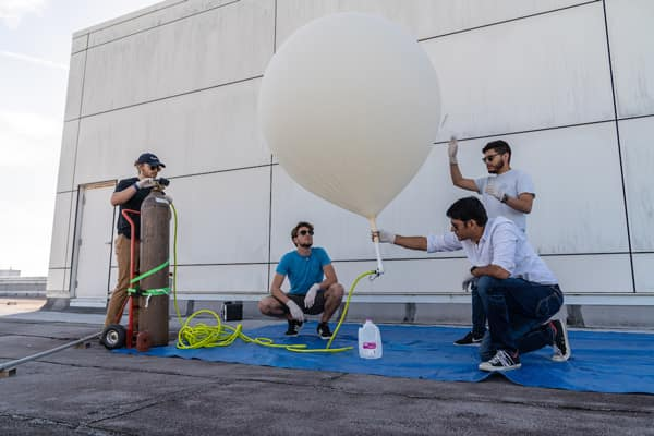 Dr. Aroh Barjatya (kneeling) and students (L-R): Christopher Swinford, Peter Douglass and Julio Guardado prepare a high-altitude balloon, which makes it possible to capture data on atmosphere turbulence.