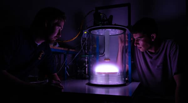 Engineering Physics graduate student Liam Gunter and Aerospace Engineering undergraduate Kyle Hrenyo peer into a newly commissioned glow-discharge plasma chamber in the Space and Atmospheric Instrumentation Lab. (Photo: Embry-Riddle/Daryl LaBello)