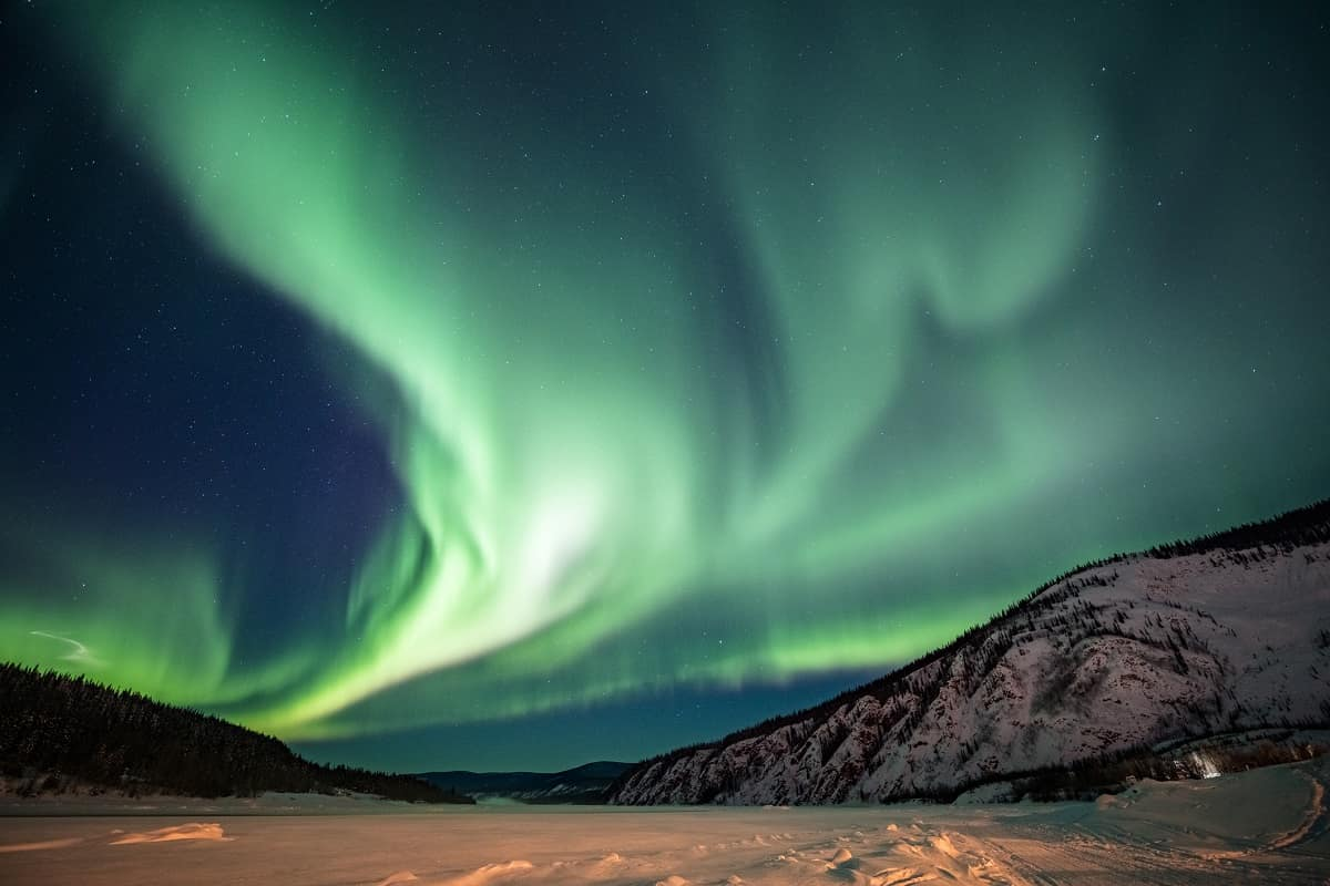 The aurora borealis, or northern lights, forms a green band, here over the Yukon Territory, in Canada.