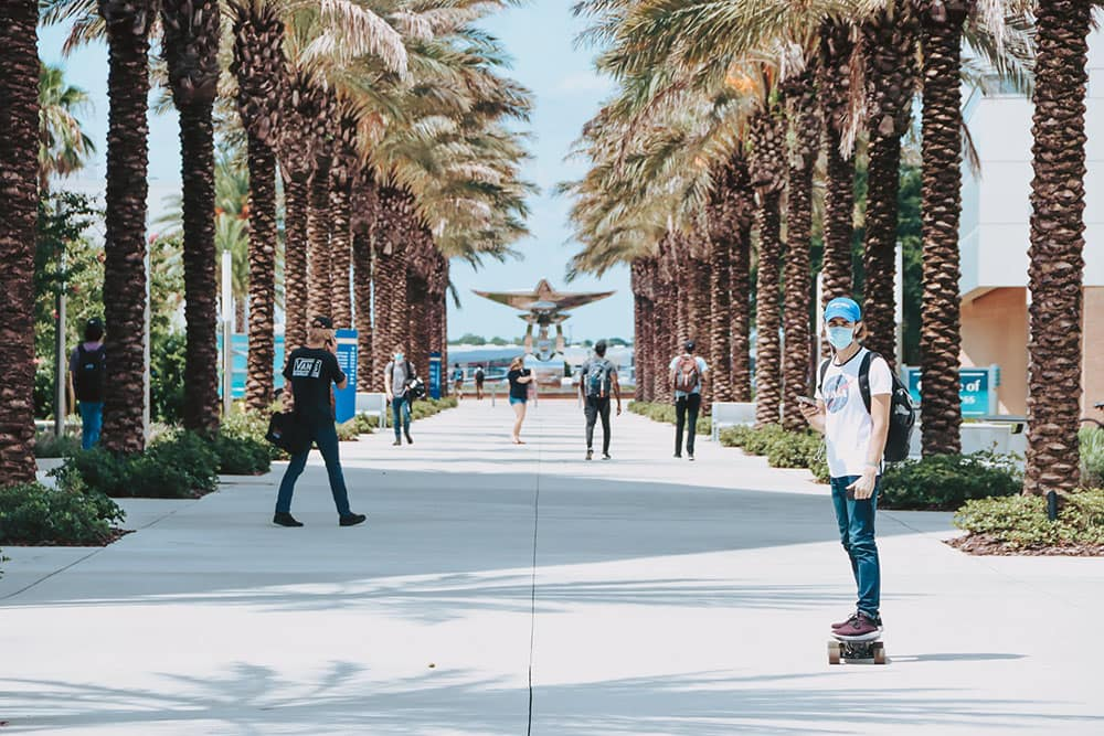 Student wearing mask rides skateboard on Embry-Riddle campus in Daytona Beach