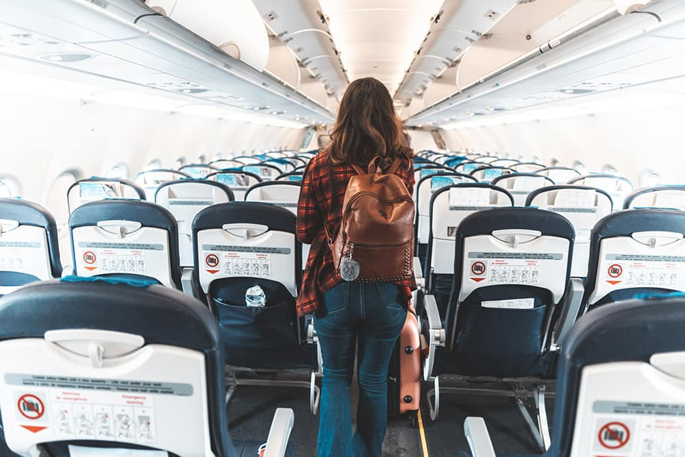 a woman boarding an empty airplane