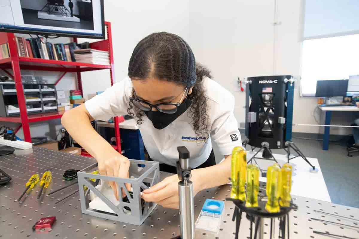 Jana Alaslani works at the optical table to assemble test components into a 3D-printed prototype of the EagleCam CubeSat camera system.