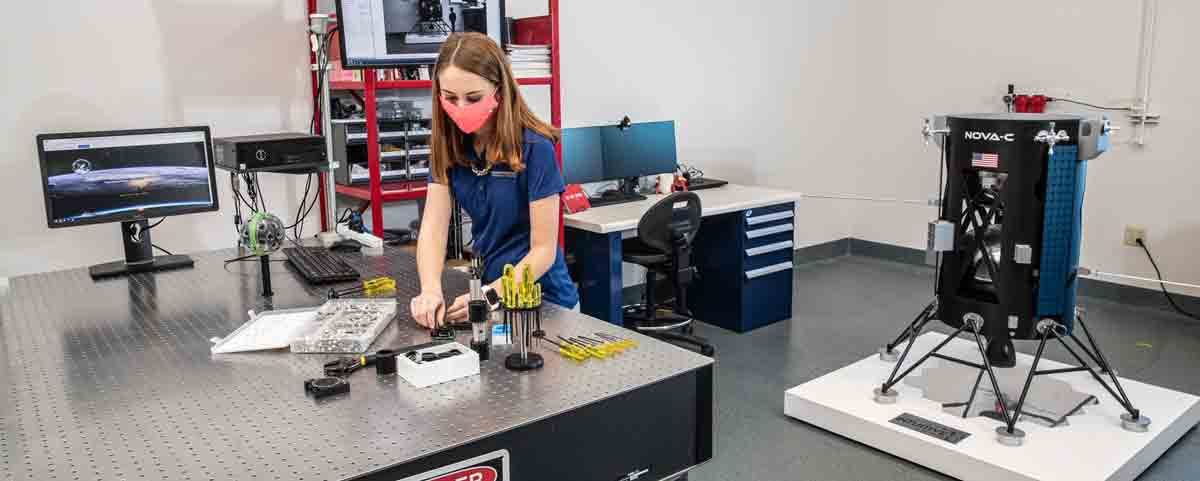 Taylor Yow, an Aerospace Engineering undergrad, examines a camera lens at the optical table in the Space Technologies Lab at Embry-Riddle Aeronautical University. The Niceville, Florida, resident works on EagleCam's sensing team and oversees project management.