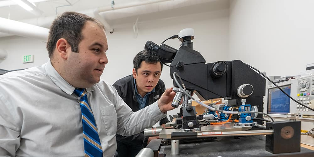 Dr. Eduardo Rojas works with PhD student Seng Loong (Hanson) on small antennas at the microscope station in the WIDE lab. January 8, 2020. (Embry-Riddle/Daryl LaBello)