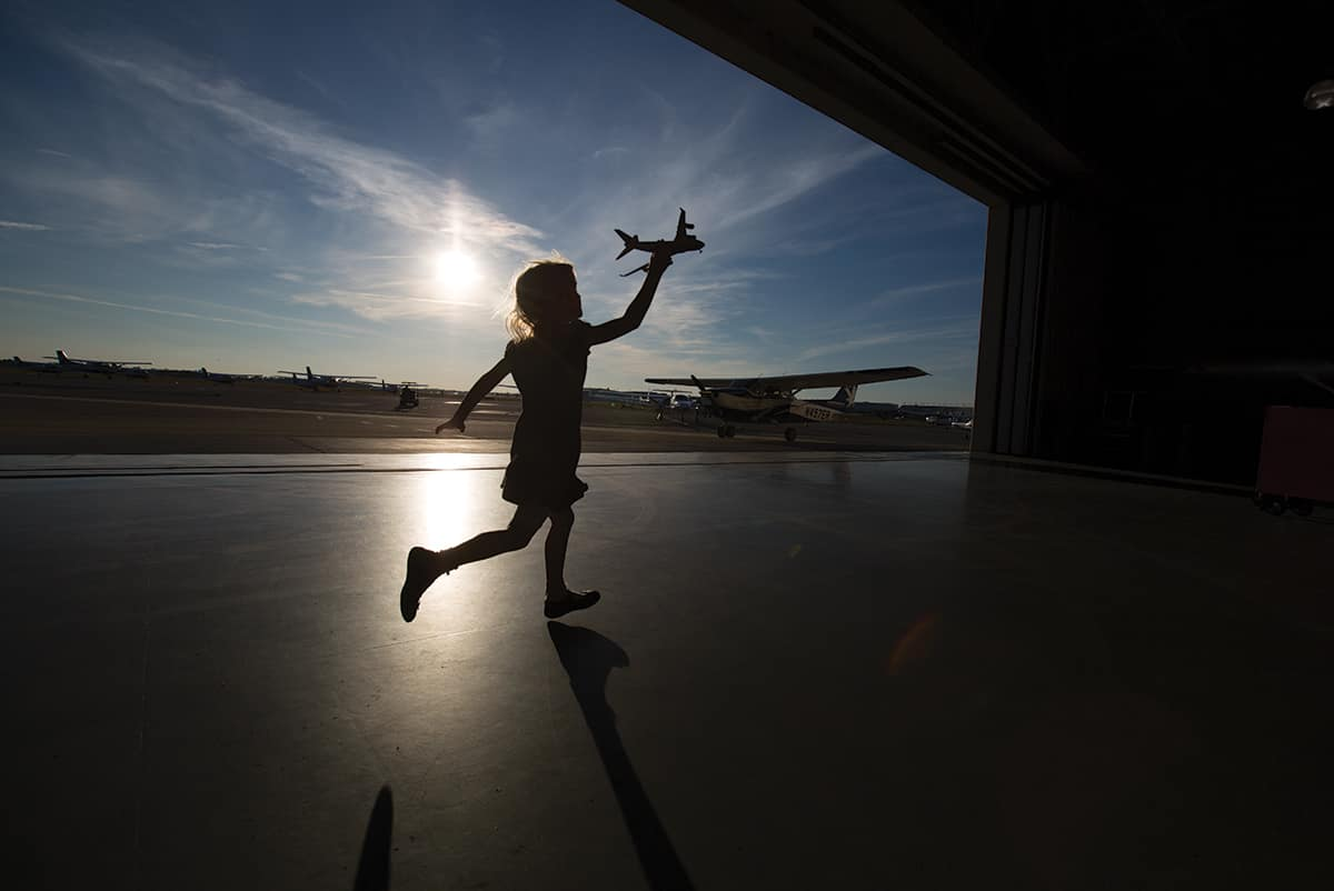 a child running with a toy airplane at a hangar