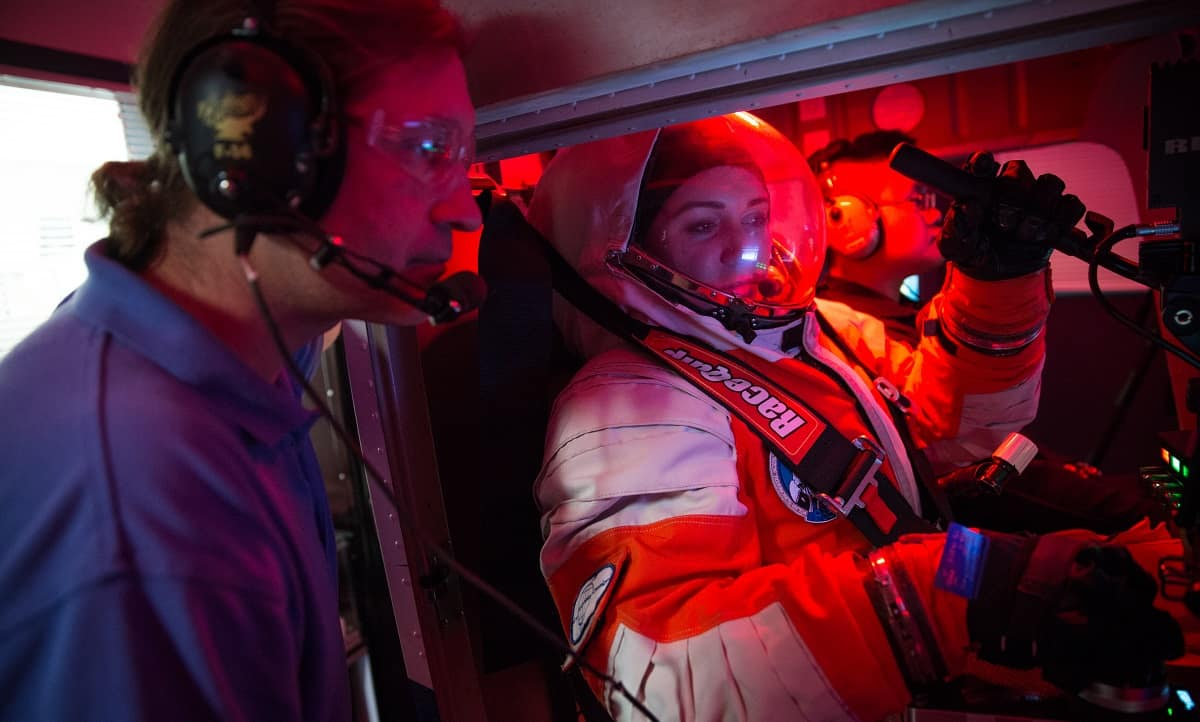 Project PoSSUM Executive Director Jason Reimuller works with student Rachel Weeks in the space-flight simulator.
