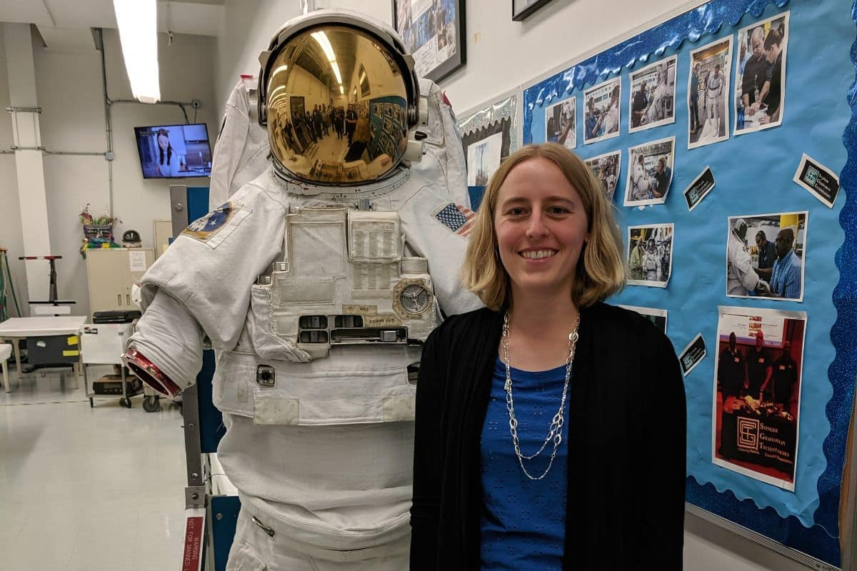 Dr. Kaela Martin standing beside a NASA space suit